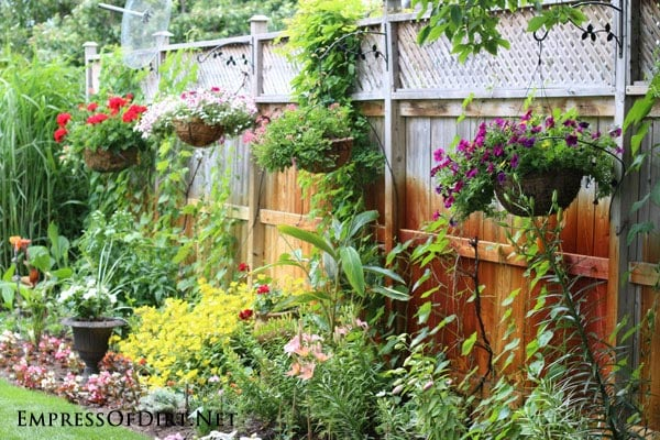 Kick your garden up a notch with these 12 Colourful Garden Ideas at empressofdirt.net. Hanging baskets of annuals add beautiful blasts of colour!