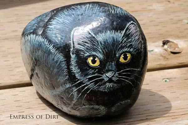 Black cat painted on a rock.