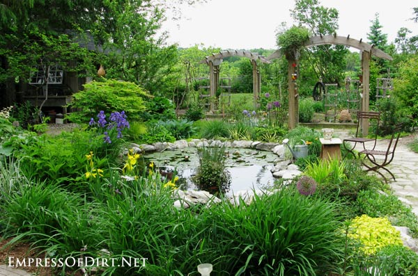Beautiful backyard pond next to a traditional Victorian kitchen garden with modern garden junk decor.