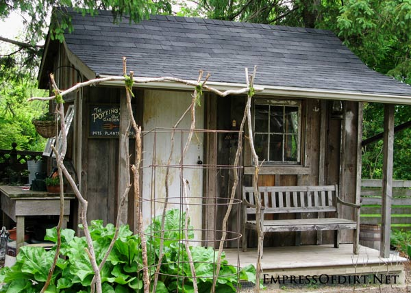 Old shed with weathered barn board in modern Victorian-style kitchen garden.
