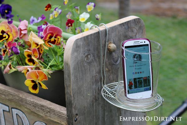 DIY mobile phone holder/protector/speaker on side of garden trug.
