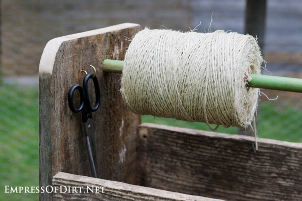 The trug handle holds a spool of garden twine with scissors on a hook nearby.
