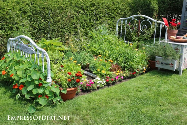 Vegetable and flower garden framed with old metal bed posts.