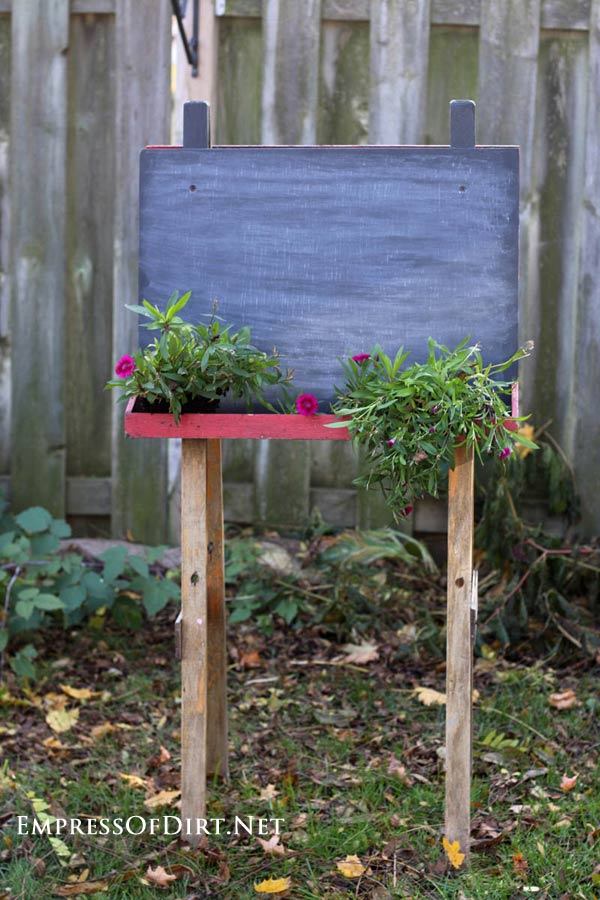 Turn an old chalkboard art easel into a plant stand. This one is used to list menus for outdoor entertaining. Come see the rest of the ideas in the Garden Art Easels gallery.