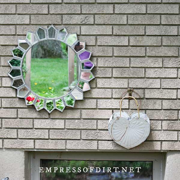 Sunburst mirror on brick wall.