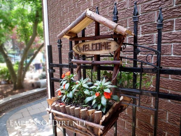 Wood branch planter hanging on metal gate at entry to side garden. A sign says welcome.