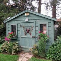 Blue garden shed with butterfly art on door.