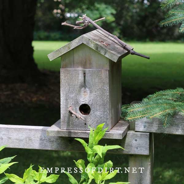 Plain wood birdhouse on fence.