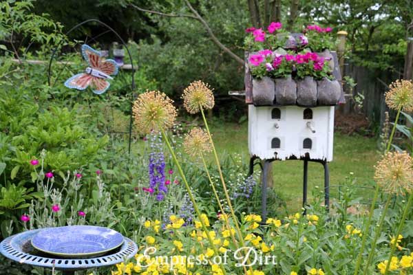 White birdhouse with flower roof and blue bird bath.