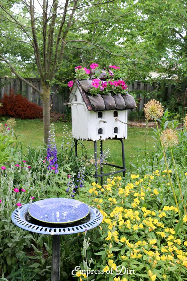 Large white bird house with flower roof and birdbath.