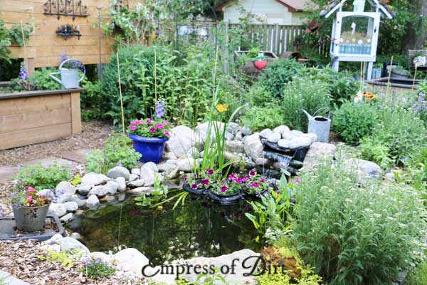 Small garden pond with floating flower planters.