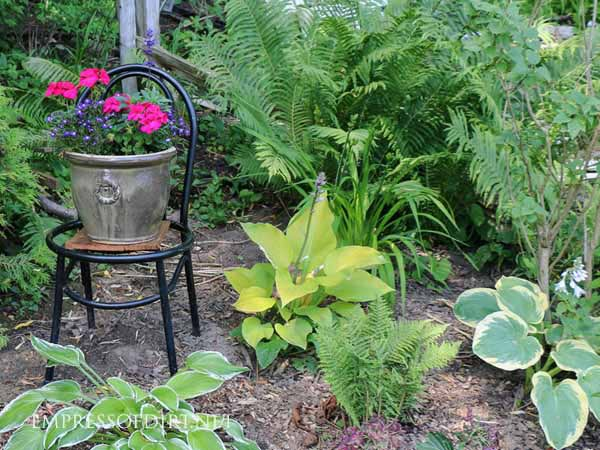 Change the height of plants and decor to liven up a shade garden.