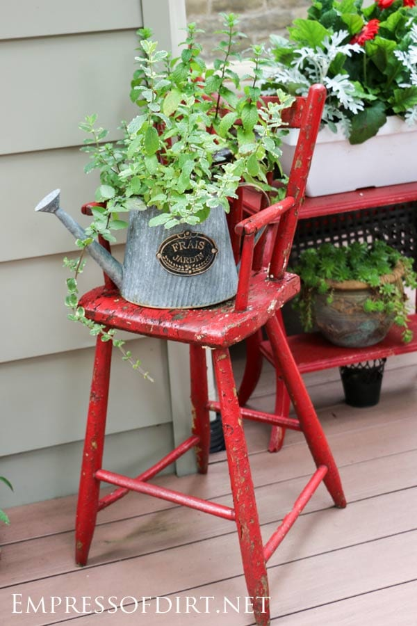 Red chair with vintage watering can and greenery.
