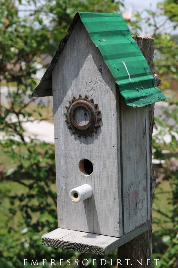 Rustic birdhouse with green tin roof.