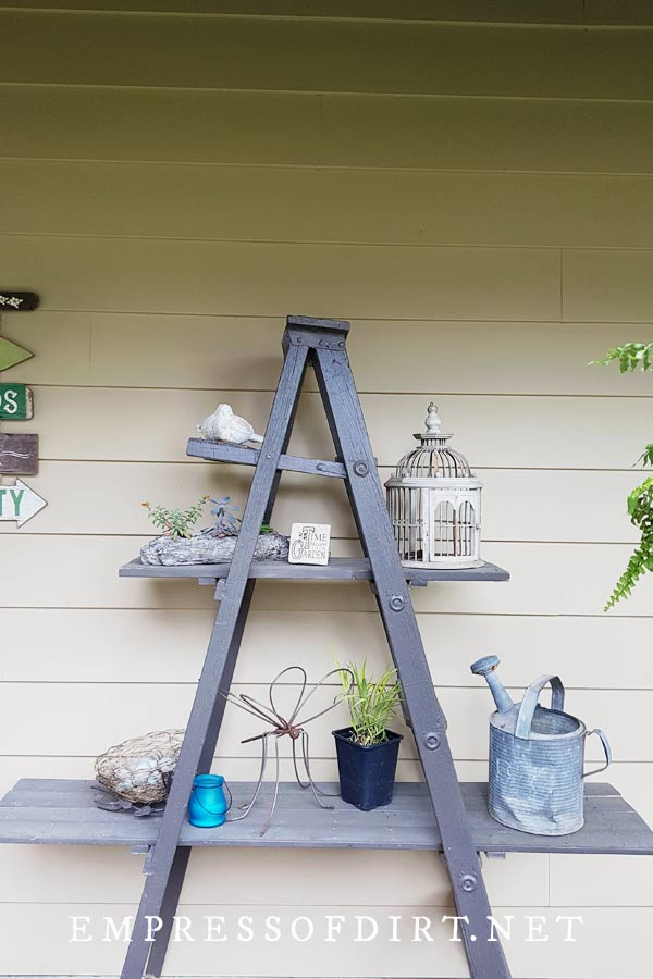 Vintage ladder with garden art on a front porch.
