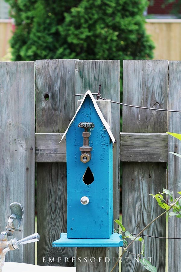 Blue garden art birdhouse with teardrop door.
