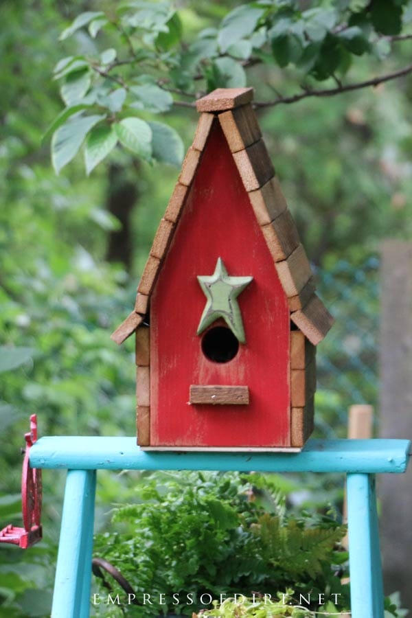 Colorful red garden art birdhouse with star door.