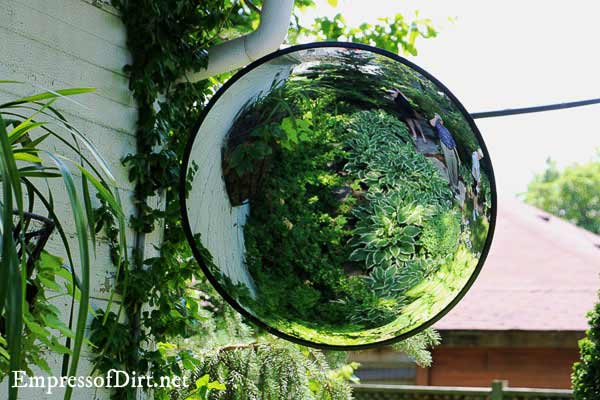 Industrial convex mirror on a garage overlooking the garden