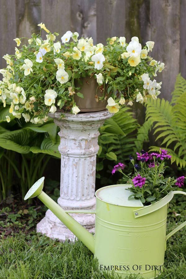 Light green watering can with flowers.
