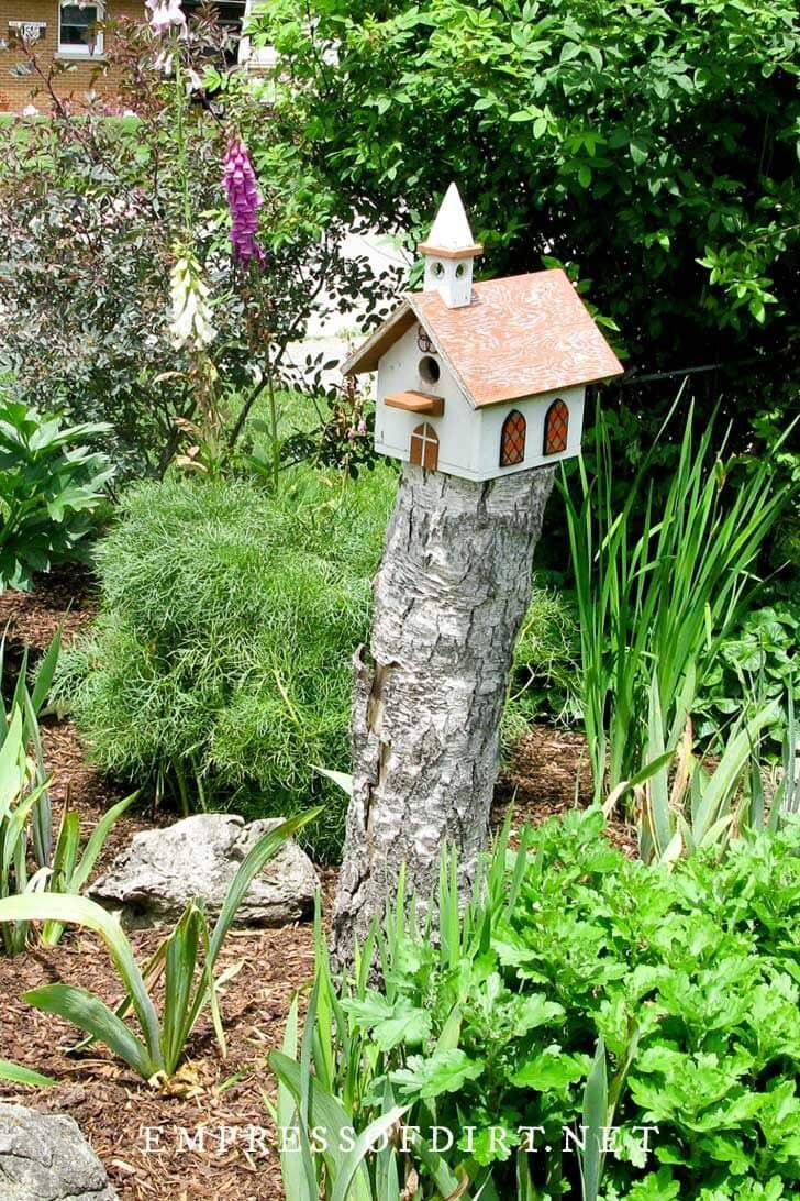 Church-like birdhouse on a tree stump in a garden.