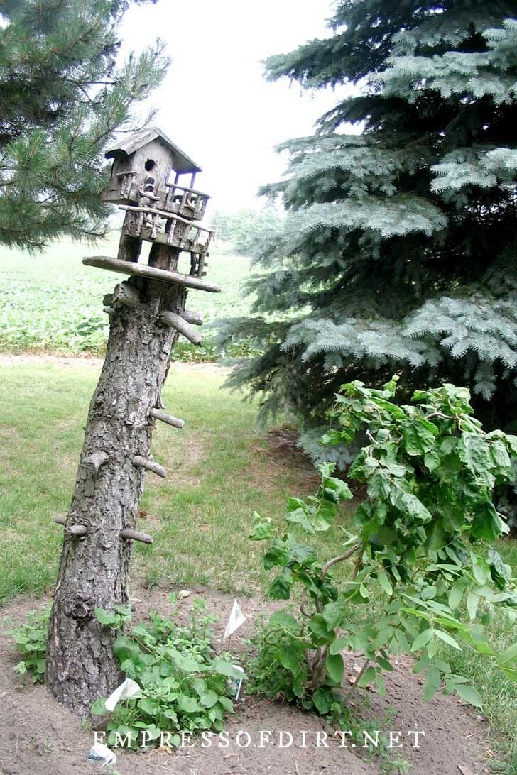 Rustic birdhouse on a tree stump in a garden.