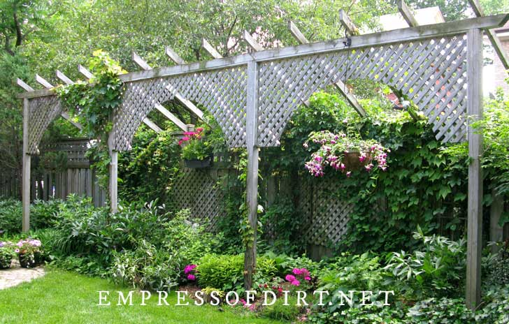 Lattice fence extension for privacy with colorful flower baskets.
