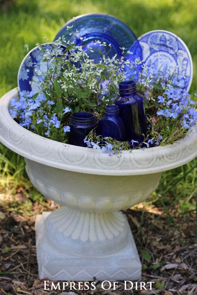 Using old dishes to decorate a garden planter.