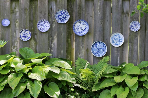 Dress up a garden fence with old plates.