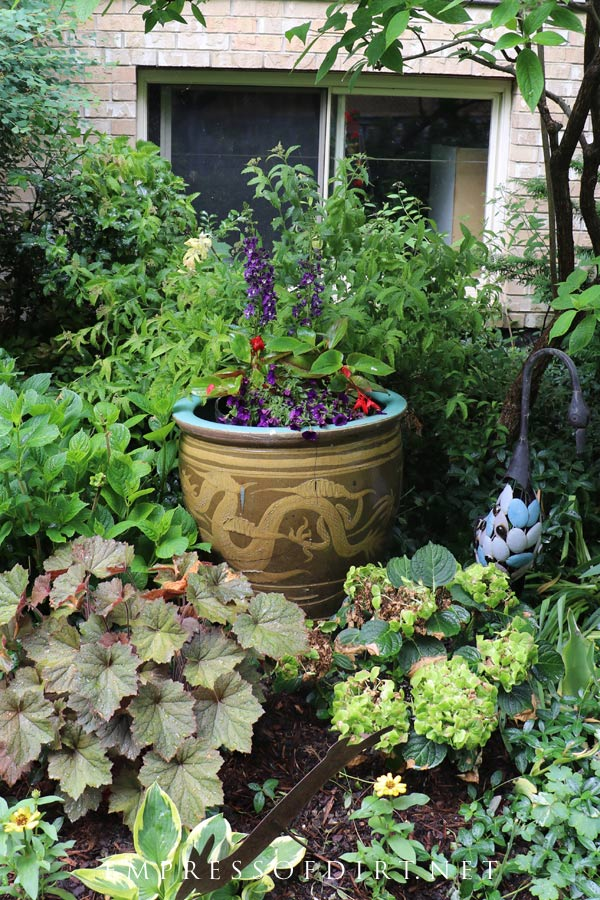 Purple and red flowers stand out in this dragon flower pot.