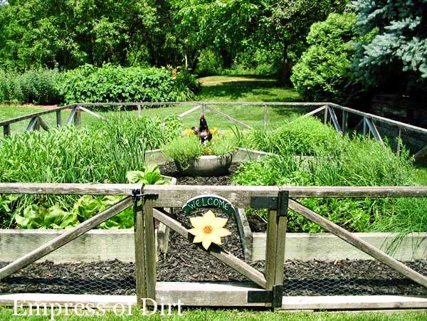 Fenced vegetable garden with raised beds and flower sign on gate.