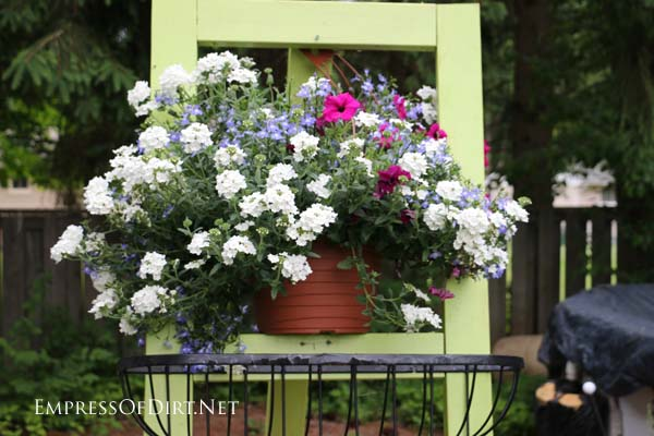 Garden art easel with potted annuals.