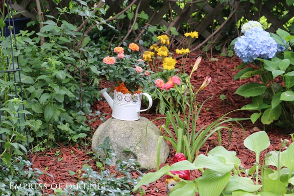 White watering can with flowers in garden.