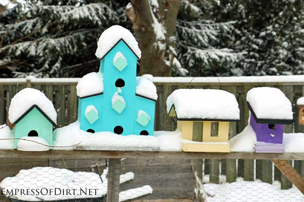 Snow on colorful birdhouses.