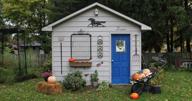 Garden shed decorated for fall with straw bales and pumpkins after paint makeover.