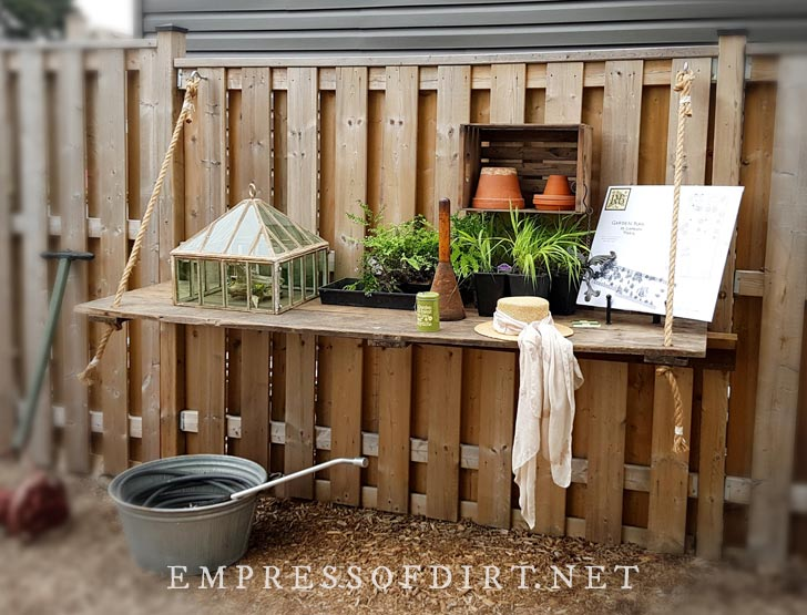 Fence shelf with rope hangers in backyard garden.