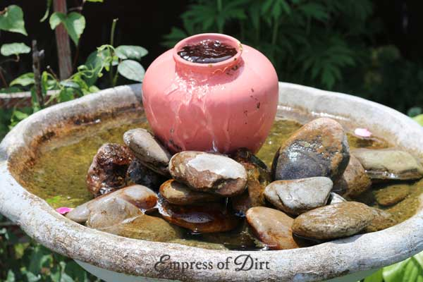 Create an overflowing fountain with a flower pot in a bird bath