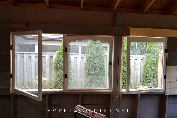 Framing windows for a lean-to greenhouse.
