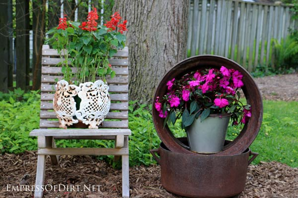 Create a garden vignette with trash day finds! Here we have a homemade wooden deck chair, a rickety white metal planter cover, a metal tire rim and big, old cooking pot.