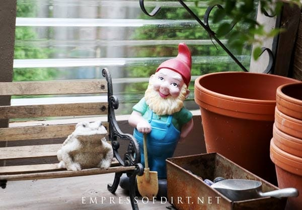 Garden gnome and toad inside DIY lean-to greenhouse.