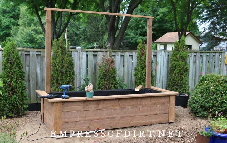 Construcción de cama de jardín elevada con soporte para postes traseros.