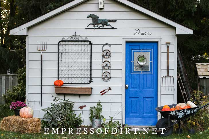 Garden shed decorated for fall with straw bales and pumpkins.