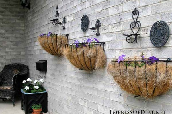 Kitchen trivets and metal candle holders can dress up a garden fence or wall.