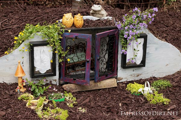 Turn a knick-knack shelf into a hobbit house for the garden.