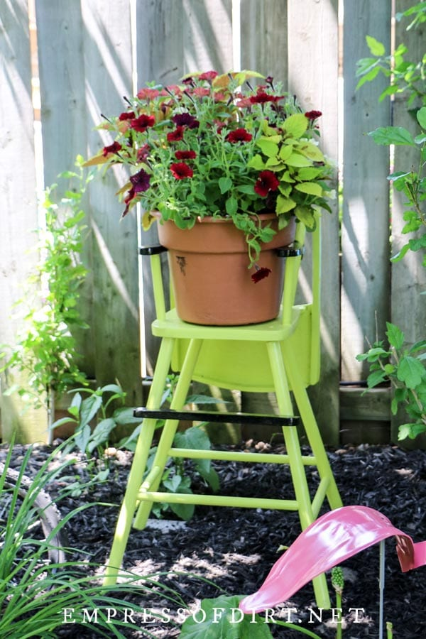 Old wooden high chair painted green for the garden.