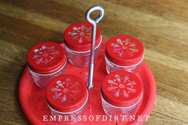 Mason jar hummingbird feeder made with plate and eye bolt.