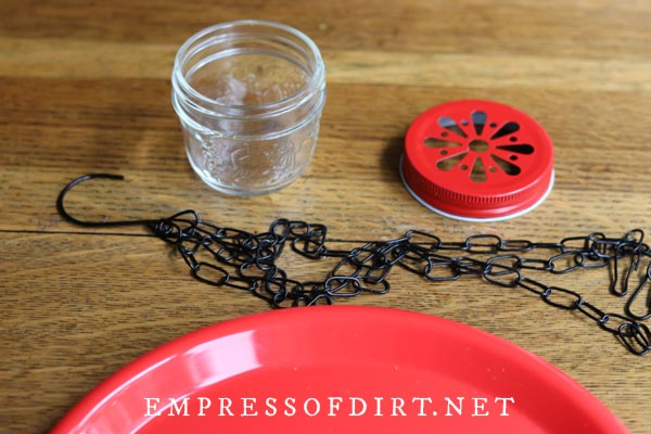 Small mason jar, red daisy lid, chains, and red plate.