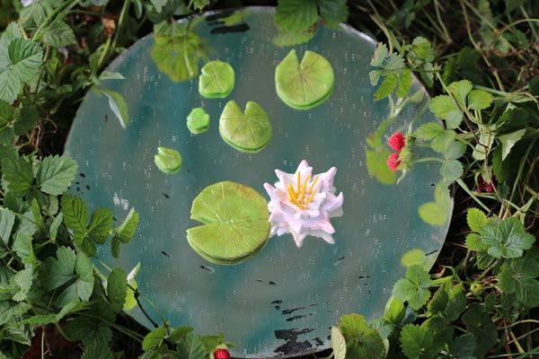 Make a miniature fairy pond using an old mirror.