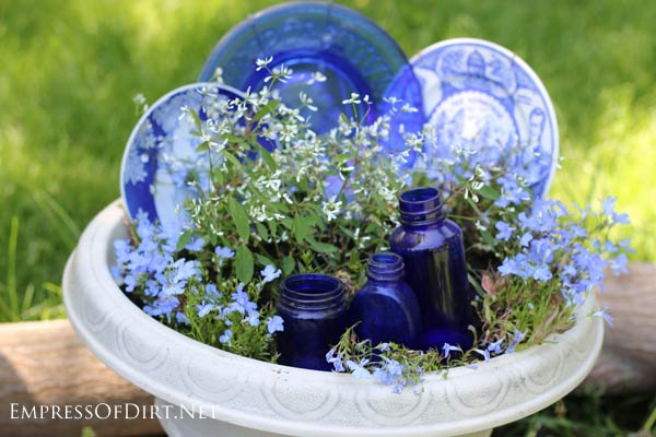 Fill in a planter with old dishes until the flowers are fully in bloom.