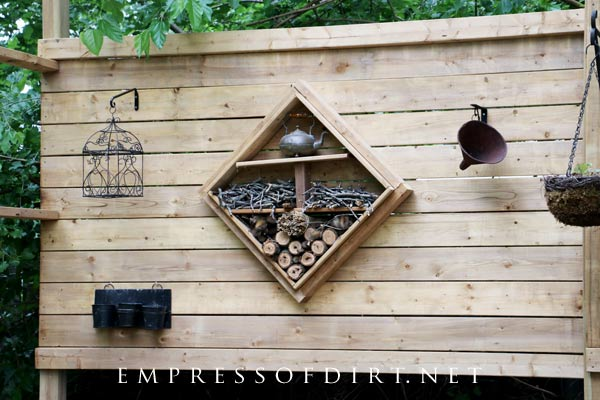 Bug hotel on wall of freestanding privacy screen.