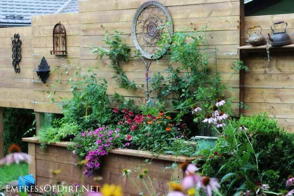 This project combines a large, raised garden bed with a privacy wall to create a sheltered location for growing plants as well as displaying garden art.